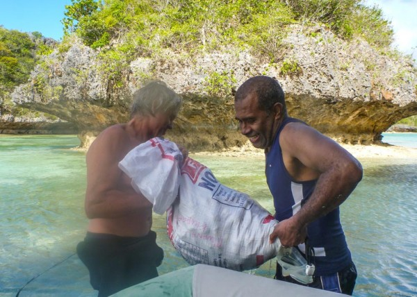 Monty and George lifting the bag of clams into the dinghy
